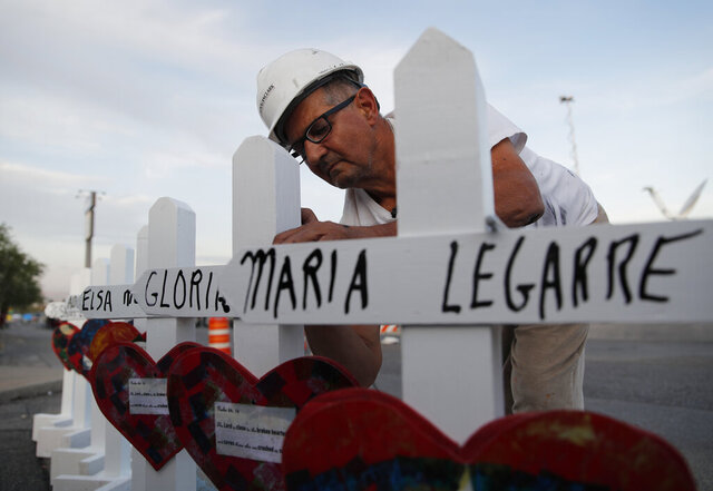 FILE - In this Aug. 5, 2019, file photo Greg Zanis prepares crosses to place at a makeshift memorial for victims of a mass shooting at a shopping complex in El Paso, Texas. The Illinois man who made and delivered more than 27,000 crosses to sites around the U.S., largely to remember victims of gun violence, is stepping away from his ministry but aims to train others to carry it on. (AP Photo/John Locher, File)