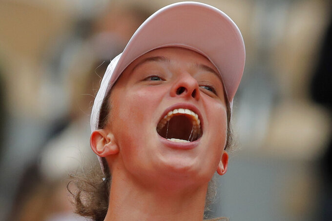 Poland's Iga Swiatek celebrates winning the final match of the French Open tennis tournament against Sofia Kenin of the U.S. in two sets, 6-4, 6-1, at the Roland Garros stadium in Paris, France, Saturday, Oct. 10, 2020. (AP Photo/Michel Euler)