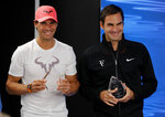 Spain's Rafael Nadal, left, and Switzerland's Roger Federer hold their trophies for International tennis Writers Association