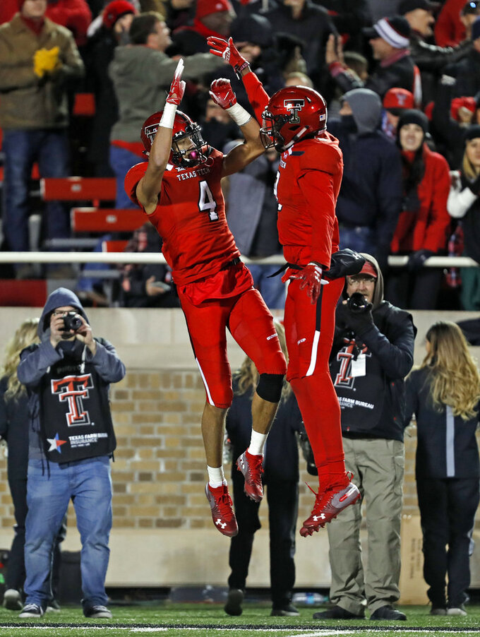 Texas Tech's Antoine Wesley (4) and T.J. Vasher (9) celebrate after a touchdown during the second half of the team's NCAA college football game against Texas, Saturday, Nov. 10, 2018, in Lubbock, Texas. (AP Photo/Brad Tollefson)