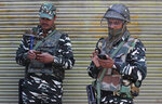 Indian paramilitary soldiers make calls from their cellphones as they guard a closed market in  Srinagar, Indian controlled Kashmir, Monday, Oct. 14, 2019.  Postpaid cellphone services were restored in India-administered Kashmir on Monday, more than two months after India's government downgraded the region's semi-autonomy and imposed a security and communications lockdown. (AP Photo/Mukhtar Khan)
