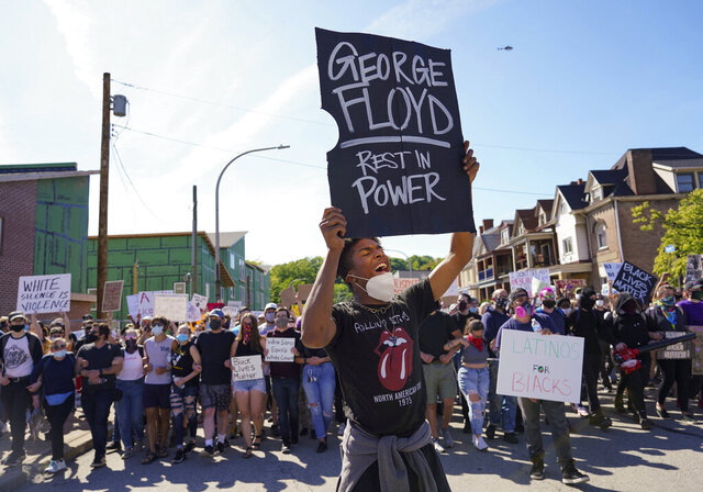 In this Monday, June 1, 2020 photo, Dínico Perry-Ellis leads a chant on Station Street in Pittsburgh, protesting the death of George Floyd, who died after being restrained by Minneapolis police officers on May 25. (Steve Mellon/Pittsburgh Post-Gazette via AP)
