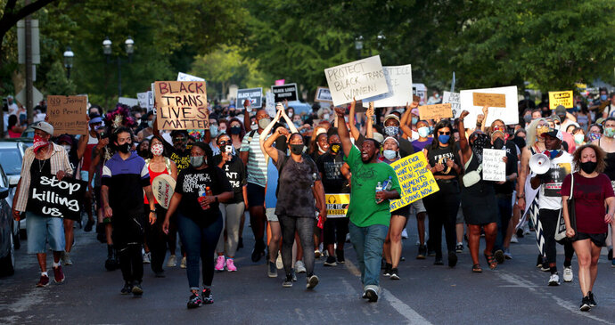 Hundreds of protesters march down Waterman Boulevard headed to St. Louis Mayor Lyda Krewson's home on Sunday, June 28, 2020, in St. Louis. The protesters demanded Krewson's resignation after she read the names and addresses of several residents who supported defunding the police department during an online briefing.    (Robert Cohen/St. Louis Post-Dispatch via AP)