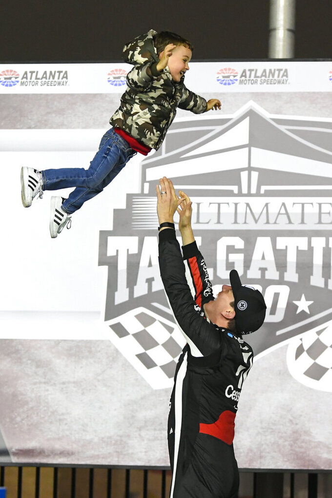 Kyle Busch tosses his son Brexton up in the air while celebrating in Victory Lane after winning the NASCAR Truck Series auto race at Atlanta Motor Speedway, Saturday, Feb. 23, 2019, in Hampton, Ga. (AP Photo/John Amis)