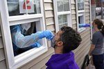 Tim Smith, of Boston, receives a free COVID-19 test given by Health Innovations, Tuesday, Dec. 1, 2020, in Chelsea, Mass. (AP Photo/Elise Amendola)