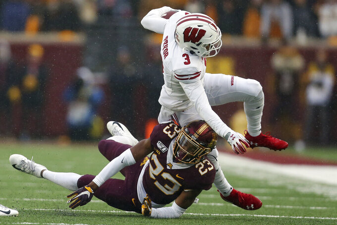 FILE- In this Nov. 30, 2019, file photo, Wisconsin wide receiver Kendric Pryor (3) is knocked down by Minnesota defensive back Jordan Howden (23) during an NCAA college football game in Minneapolis. Wisconsin is cautiously optimistic that a year full of adversity on and off the field will help its passing attack live up to the promise it showed last season. (AP Photo/Stacy Bengs, File)