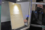Ella Hall, a specialist in Books and Manuscripts, at Sotheby's, in New York, places a 1787 printed copy of the U.S. Constitution in its display case, Friday, Sept. 17, 2021. Sotheby's announced Friday — appropriately on Constitution Day — that in November it will put up for auction one of just 11 surviving copies of the Constitution from the official first printing produced for the delegates to the Constitutional Convention and for the Continental Congress. It's the only copy that remains in private hands and has an estimate of $15 million-$20 million. (AP Photo/Richard Drew)