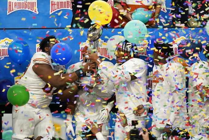 Texas players celebrate their win over Colorado in the Alamo Bowl NCAA college football game, early Wednesday, Dec. 30, 2020, in San Antonio. (AP Photo/Eric Gay)