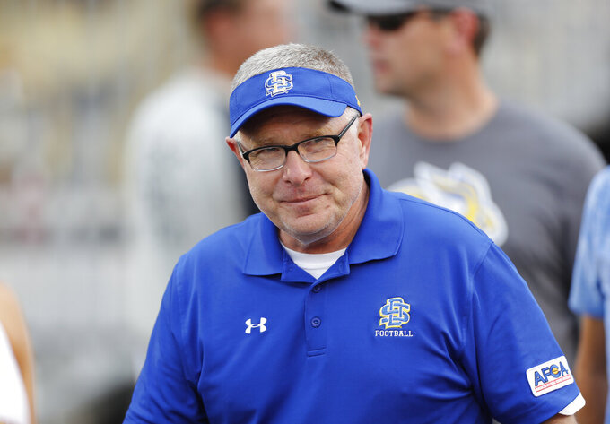 FILE - In this Sept. 1, 2018, file photo, South Dakota State head coach John Stiegelmeier smiles as he enters the field for an NCAA college football game against Iowa State, in Ames, Iowa. Top-seeded South Dakota State takes on No. 2 seed Sam Houston on Sunday, May 16, 2021, guaranteeing that one of those Football Championship Subdivision playoff regulars will become a first-time champion.(AP Photo/Matthew Putney, File)