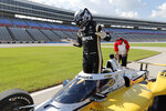 Josef Newgarden gestures as he stands up in the cockpit after earning the pole position for an IndyCar auto race at Texas Motor Speedway in Fort Worth, Texas, Saturday, June 6, 2020. (AP Photo/Tony Gutierrez)