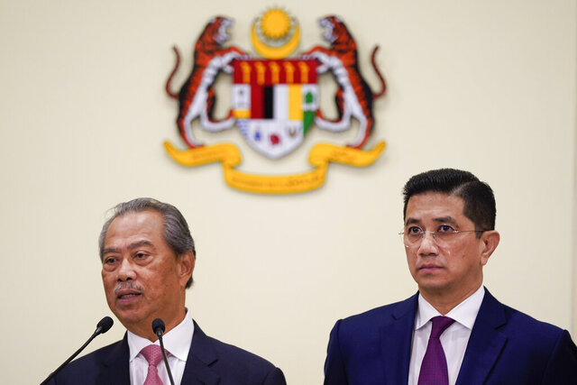 Malaysian new Prime Minister Muhyiddin Yassin, left, speaks next to Senior Minister Azmin Ali during a press conference after the first cabinet meeting at the prime minister's office in Putrajaya, Malaysia Wednesday, March 11, 2020. Yassin said he will form an economic council to find ways to cope with an expected economic slowdown amid the global new coronavirus outbreak. (AP Photo/Vincent Thian)