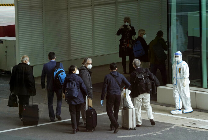 Members of the World Health Organization (WHO) team arrive at the airport in Wuhan in central China's Hubei province on Thursday, Jan. 14, 2021. A global team of researchers arrived Thursday in the Chinese city where the coronavirus pandemic was first detected to conduct a politically sensitive investigation into its origins amid uncertainty about whether Beijing might try to prevent embarrassing discoveries. (AP Photo/Ng Han Guan)