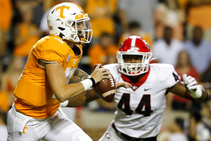 Tennessee quarterback Brian Maurer (18) looks to evade Georgia defensive lineman Travon Walker (44) at Neyland Stadium on Saturday, Oct. 5, 2019 in Knoxville, Tenn.(C.B. Schmelter/Chattanooga Times Free Press via AP)