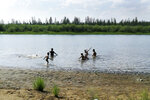 In this handout photo taken Sunday, June 21, 2020 and provided by Olga Burtseva, children play in the Krugloe lake outside Verkhoyansk, the Sakha Republic, about 4660 kilometers (2900 miles) northeast of Moscow, Russia. A record-breaking temperature of 38 degrees Celsius (100.4 degrees Fahrenheit) was registered in the Arctic town of Verkhoyansk on Saturday, June 20 in a prolonged heatwave that has alarmed scientists around the world. (Olga Burtseva via AP)