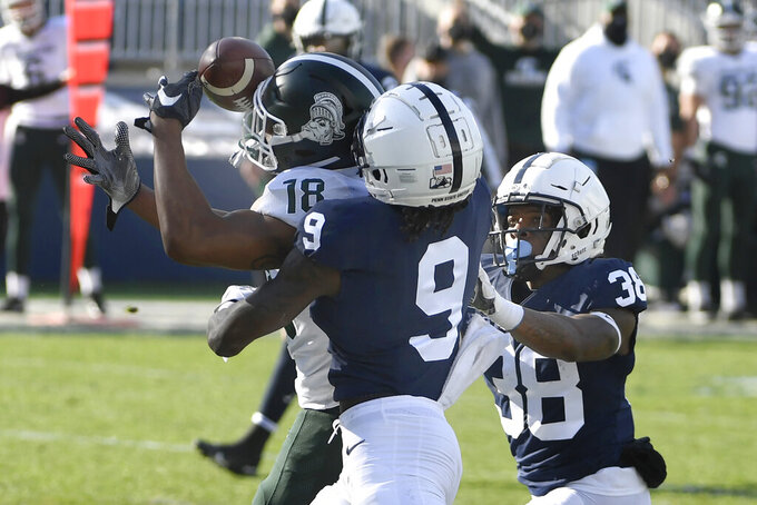 Michigan State wide receiver Tre'Von Morgan (18) catches a touchdown pass over Penn State cornerback Joey Porter Jr. (9) during the second quarter of an NCAA college football game in State College, Pa., on Saturday, Dec. 12, 2020. (AP Photo/Barry Reeger)
