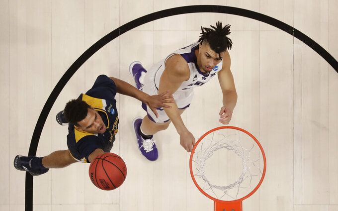 UC Irvine guard Evan Leonard, left, shoots against Kansas State guard Mike McGuirl during the first half of a first round men's college basketball game in the NCAA Tournament Friday, March 22, 2019, in San Jose, Calif. (AP Photo/Ben Margot)