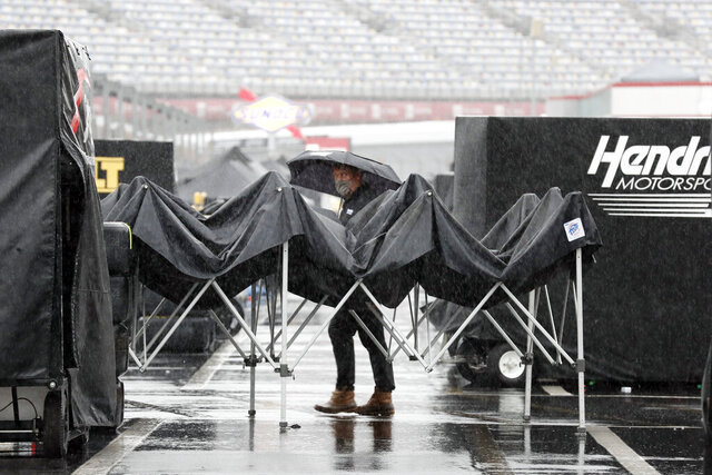 A man walks through the infield as rain falls before a NASCAR Cup Series auto race at Charlotte Motor Speedway Wednesday, May 27, 2020, in Concord, N.C. (AP Photo/Gerry Broome)