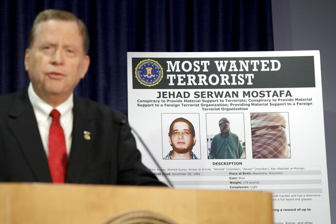 U.S Attorney Robert Brewer speaks in front of an FBI poster depicting Jehad Serwan Mostafa during a news conference Monday, Dec. 2, 2019, in San Diego. The U.S. attorney's office in San Diego says the 37-year-old U.S. citizen who is on the FBI's Most Wanted Terrorist List is facing a new indictment. (AP Photo/Gregory Bull)