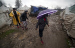 Migrants walk in the Vucjak refugee camp outside Bihac, northwestern Bosnia, Saturday, Nov. 16, 2019.  A storm in Bosnia has swept through a bleak make-shift camp for migrants who are trying to reach Western Europe, blowing many tents away. (AP Photo/Almir Alic)