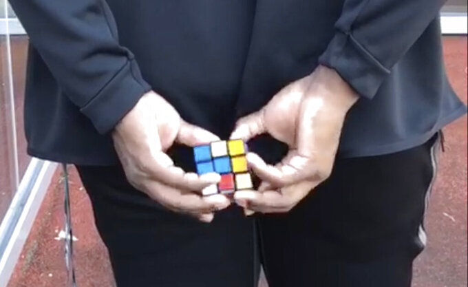 CORRECTS TO BEING CLAIMED OFF WAIVERS FROM THE PATRIOTS, NOT AS AN UNDRAFTED FREE AGENT FROM THE UNIV. OF TEXAS - In this image taken from video, New York Jets rookie offensive lineman Calvin Anderson works on a Rubik's Cube behind his back at the NFL football team's practice facility in Florham Park, N.J., Sunday, July 28, 2019. The puzzle cubes are a bit of an obsession for Anderson, who was claimed off waivers from the Patriots after New England signed him as an undrafted free agent. (AP Photo/Dennis Waszak)