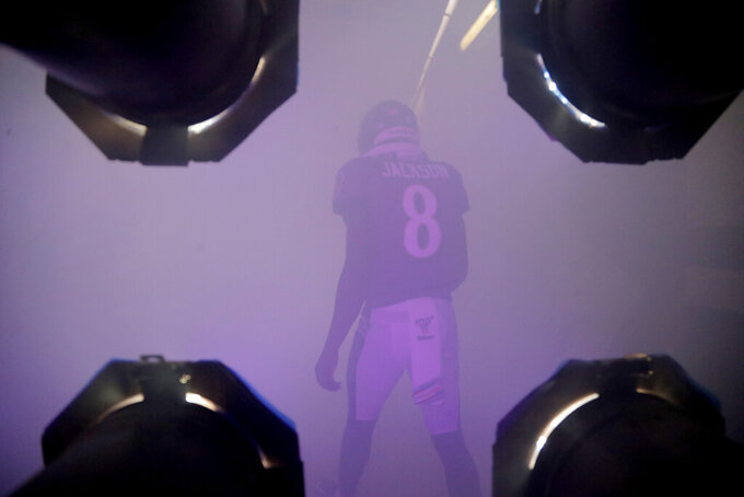 Baltimore Ravens quarterback Lamar Jackson walks through a smoke-filled tunnel while being introduced onto the field prior to an NFL football game against the Cincinnati Bengals Sunday, Oct. 13, 2019, in Baltimore. (AP Photo/Julio Cortez)