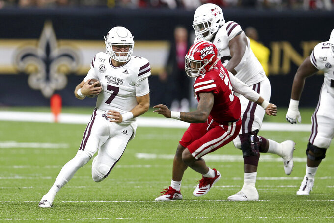 Mississippi State quarterback Tommy Stevens (7) runs from Louisiana-Lafayette linebacker Joe Dillon (3) in the first quarter of an NCAA college football game in New Orleans, Saturday, Aug. 31, 2019. (AP Photo/Chuck Cook)