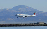 FILE - In this Oct. 24, 2017 file photo, an Air Canada plane prepares to land on a runway at San Francisco International Airport in San Francisco. Video captured the moment that an off-course Air Canada jet flew just a few dozen feet over the tops of four other jetliners filled with passengers. On Tuesday, Sept. 25, 2018, the National Transportation Safety Board will consider the probable cause of the close call at the airport. Plane pictured is not the plane the NTSB will review. (AP Photo/Jeff Chiu, File)