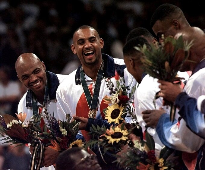 FILE - In this Aug. 3, 1996 file photo, Dream Team members Charles Barkley, left, and Grant Hill share a laugh with teammates after receiving their gold medals at the Centennial Summer Olympic Games in Atlanta.  USA Basketball announced Saturday, April 3, 2021, that  Hill will take over as managing director of the men's national team after this summer's Tokyo Olympics.   (AP Photo/Hans Deryk, File)