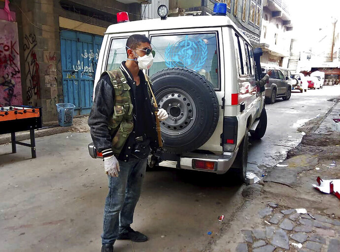 This May 2020 photo provided by a Yemeni Community activist, shows an activist waiting for an ambulance to collect the body of a COVID-19 victim, after medics declined to take the body, in the Houthi-controlled city of Ibb, Yemen. An investigation by The Associated Press found that the coronavirus is taking a deadly toll on the war weary population of Yemen. The situation is exacerbated in the Houthi-controlled north where the rebels have suppressed information about the virus, severely punished those who speak out, enforced little mitigation measures, and promoted conspiracies and claims by the Houthi minister of health that scientists are working on developing a cure for covid-19 to present to the world. (Courtesy of a Yemeni Community Activist via AP)