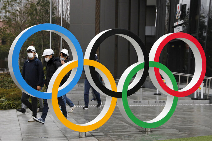 FILE - In this March 4, 2020, file photo, people wearing masks walk past the Olympic rings near the New National Stadium in Tokyo. U.S. Olympic hopefuls will be able to cut their own deals with the U.S. Olympic and Paralympic Committee's marketing partners under a first-of-its-kind plan that has potential to shift the top-heavy sponsorship model that rules the Olympic world.(AP Photo/Jae C. Hong, File)