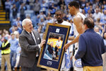 North Carolina coach Roy Williams is presented with a photograph of himself with Dean Smith by players Brandon Robinson and Garrison Brooks following an NCAA college basketball game in Chapel Hill, N.C., Monday, Dec. 30, 2019. Williams tied Dean Smith with 879 careers wins. (AP Photo/Gerry Broome)