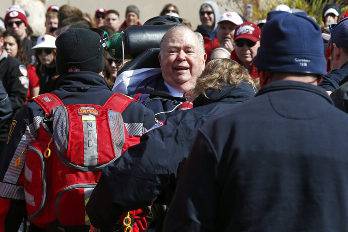 David Boren, president of the University of Oklahoma, is taken away by medical personnel and security during the unveiling of a statue of former head football coach Bob Stoops in Norman, Okla., Saturday, April 14, 2018. (AP Photo/Sue Ogrocki)