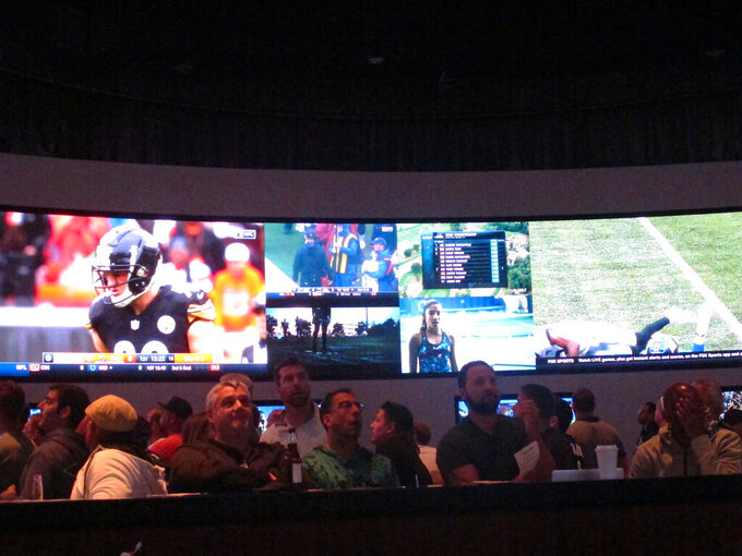 Football fans watch the action on wall-mounted video screens in the sports betting lounge at the Ocean Resort Casino in Atlantic City, N.J. on Sunday Sept. 9, 2018. The coronavirus virus outbreak has added new wrinkles for bettors this year,but even so, the nation's sports books expect a record year of bets on football in 2020 from an antsy public that has been cooped up for months amid the pandemic. (AP Photo/Wayne Parry)