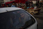 Two Afghans sit inside the trunk of a car in Kabul's Old City, Afghanistan, Tuesday, Sept. 14, 2021. It is feared Afghanistan could further plunge toward famine and economic collapse after the chaos of the past month, which saw the Taliban oust the government in a lightning sweep as U.S. and NATO forces exited the 20-year war. (AP Photo/Bernat Armangue)