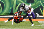 Baltimore Ravens' Marquise Brown (15) stiff-arms Cincinnati Bengals cornerback LeShaun Sims (38) to the ground as he returns a punt during the first half of an NFL football game, Sunday, Jan. 3, 2021, in Cincinnati. (AP Photo/Aaron Doster)