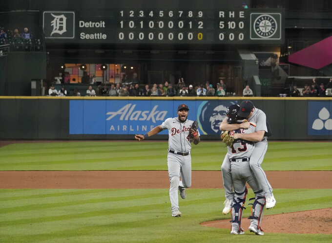 Detroit Tigers starting pitcher Spencer Turnbull, right, hugs catcher Eric Haase as third baseman Jeimer Candelario rushes to join them after Turnbull threw a no-hitter in the team's baseball game against the Seattle Mariners, Tuesday, May 18, 2021, in Seattle. The Tigers won 5-0. (AP Photo/Ted S. Warren)