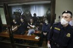Members of the New Greatness group, who are charged with the organisation of an extremist association, sit behind a glass in a courtroom prior to a court hearing in Moscow, Russia, Tuesday, July 14, 2020. Members of an opposition group dubbed New Greatness were arrested in 2018 on charges of creating an extremist group aiming to overthrow the government. The case was widely criticized as an example of politically motivated abuse anti-extremism laws. (AP Photo/Pavel Golovkin)