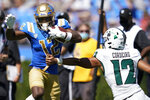 UCLA defensive back Martell Irby (12) runs to the end zone for a touchdown past Hawaii quarterback Chevan Cordeiro (12) during the second half of an NCAA college football game Saturday, Aug. 28, 2021, in Pasadena, Calif. (AP Photo/Ashley Landis)