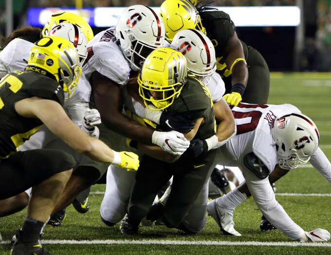 Oregon's Cyrus Habibi-Likio, center, plows into the end zone for a touchdown during the fourth quarter of an NCAA college football game Saturday, Nov. 7, 2020, in Eugene, Ore. (AP Photo/Chris Pietsch)
