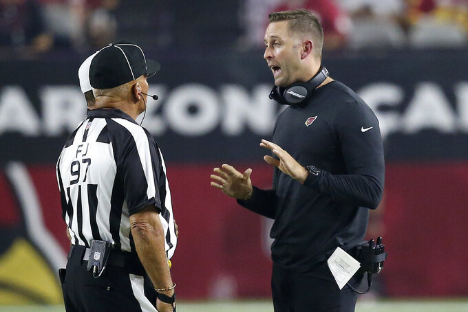 Arizona Cardinals head coach Kliff Kingsbury talks with field judge Tom Hill (97) during the first half of an NFL preseason football game against the Los Angeles Chargers, Thursday, Aug. 8, 2019, in Glendale, Ariz. (AP Photo/Ross D. Franklin)