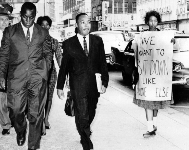 FILE - In this Oct. 19, 1960 file photo, Dr. Martin Luther King Jr. under arrest by Atlanta Police Captain R.E. Little, left rear, passes through a picket line outside Rich's Department Store, in atlanta. On King's right are Atlanta Student Movement leader Lonnie King and Spelman College student Marilyn Pryce. Holding the sign is Spelman student activist Ida Rose McCree. Following the publication of