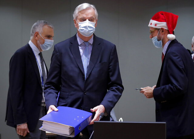 FILE - In this Friday, Dec. 25, 2020 file photo, a colleague wears a Christmas hat as European Union chief negotiator Michel Barnier, center, carries a binder of the Brexit trade deal during a special meeting of Coreper, at the European Council building in Brussels. The European Union and the United Kingdom made public Saturday the vast agreement that is likely to govern future trade and cooperation between them from Jan. 1, setting the 27-nation bloc's relations with its former member country and neighbor on a new but far more distant footing. (Olivier Hoslet, Pool via AP, File)