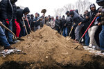 Mourners shoveled dirt onto the grave of Amatalah Adam, after her shrouded body was placed inside for burial at the Garden of Eden Islamic Cemetery, Thursday, Nov. 28, 2019, in Burnsville, Minn. Multiple people died, including Adam, and several others were injured in the early Wednesday morning blaze at the Cedar High Apartments located in a heavily immigrant neighborhood. (Leila Navidi/Star Tribune via AP)