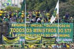 """Supporters of Brazil's President Jair Bolsonaro, displaying a banner that reads in Portuguese """"We Demand the Immediate Dismissal of All Supreme Court Ministers and Criminalization of Communism,"""" protest in front of the barrier set up by the military police after they threatened to break into the Supreme Court headquarters, in Brasilia, Brazil, Wednesday, Sept. 8, 2021. (AP Photo/Eraldo Peres)"""