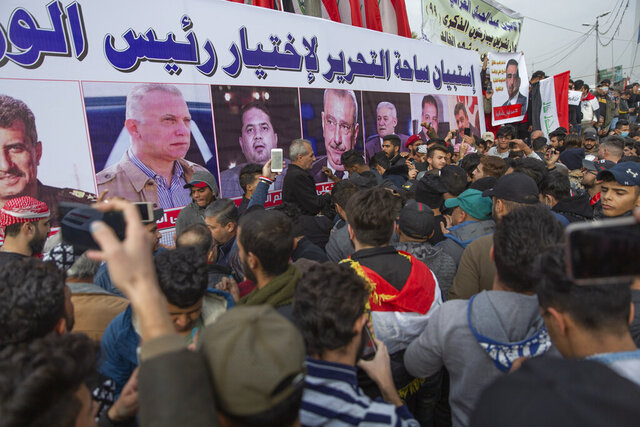 Anti government Iraqi protesters gather by a banner with pictures of Iraqi politicians and Arabic that reads