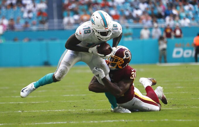 Washington Redskins wide receiver Trey Quinn (18) tackles Miami Dolphins wide receiver Preston Williams (18), during the second half at an NFL football game, Sunday, Oct. 13, 2019, in Miami Gardens, Fla. (AP Photo/Brynn Anderson)