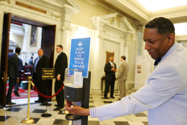 Del. Keith Haynes, a Baltimore Democrat, reaches for hand sanitizer on the last day of a shortened legislative session due to coronavirus on Wednesday, March 18, 2020, in Annapolis, Md. The Maryland General Assembly is expediting priority bills to adjourn 19 days before its previously scheduled ending on April 6. (AP Photo/Brian Witte)