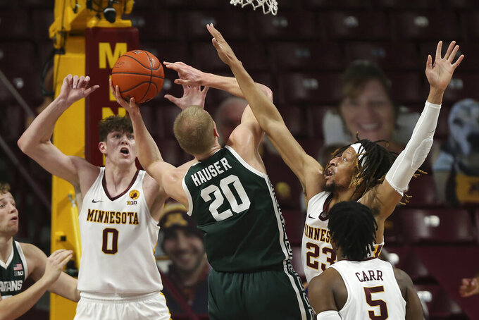 Minnesota's Brandon Johnson (23) fouls Michigan State's Joey Hauser (20) during the first half of an NCAA college basketball game Monday, Dec. 28, 2020, in Minneapolis. (AP Photo/Stacy Bengs)
