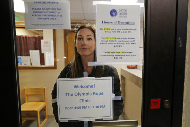 CORRECTS TO CAPITAL, NOT CAPITOL- In this Nov. 14, 2019 photo, Jamie Cline poses for a photo behind a glass window in a door at the Olympia Bupe Clinic at the Capital Recovery Center in Olympia, Wash., which helps people addicted to heroin and other opiates get prescriptions for buprenorphine, a medicine that prevents withdrawal sickness in people trying to stop using opiates. At the clinic, a doctor is working to spread a philosophy called