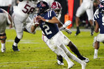 Mississippi quarterback Matt Corral (2) avoids a tackle by Alabama's Christopher Allen as he looks to pass during the first half of an NCAA college football game in Oxford, Miss., Saturday Oct. 10, 2020. Alabama won 63-48.(AP Photo/Rogelio V. Solis)